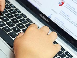 ビタミンCの摂取量をパソコンで検索する男性