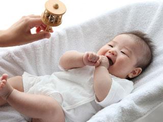 母親の振るガラガラを見て笑う赤ちゃん