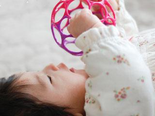 玩具を手でつかんで遊ぶ赤ちゃん