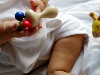 ガラガラを手に持つ赤ちゃん