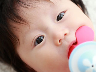 玩具を口に咥える赤ちゃん