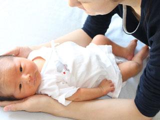 赤ちゃんの体を両手で支えるように触る母親