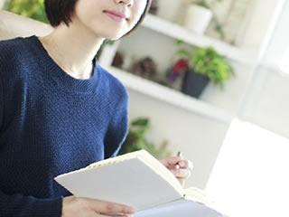 食品の危険性を本で調査する女性