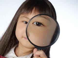 アレルギーの有無を虫眼鏡で確認する子供