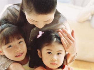 子供を背後から抱いて話しかける母親