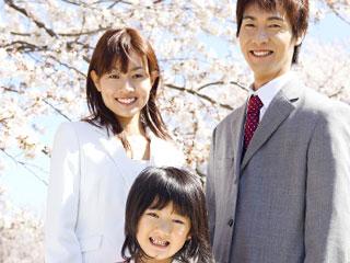 桜の前に立つ小学生と両親