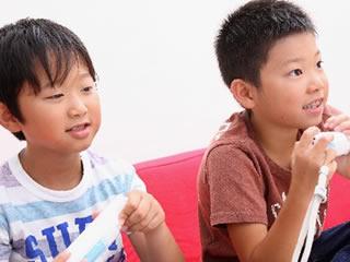 友達とゲームで対決する反抗期の小学生