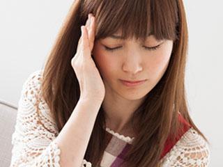 頭痛で頭に手を当てる女性