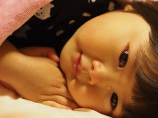 親の愛情不足を感じて布団で悲しい顔をする子供