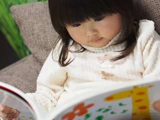 絵本を読みながら幼稚園で親の向かえを待つ子供