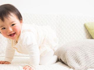 ソファの上で笑う赤ちゃん