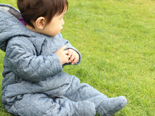 公園の芝生の上でお座りする赤ちゃん