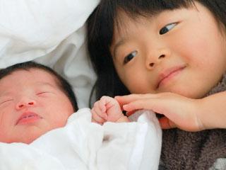赤ちゃんの横で見守るお姉さん