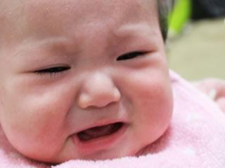 下痢の症状があり渋い表情をする赤ちゃん