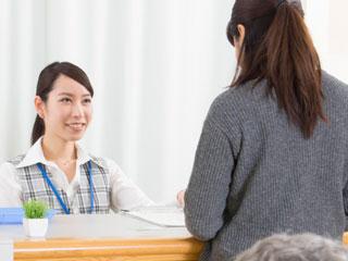 病院の窓口で支払う女性