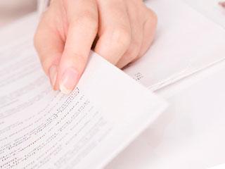書類をめくる女性の指