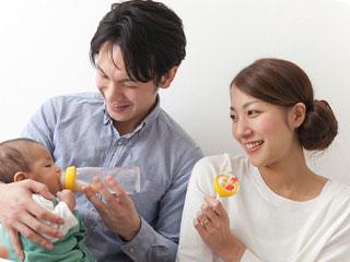 育児を手伝う夫の横で笑顔の女性