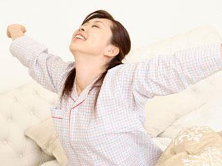 朝、寝台に座って体を伸ばす女性
