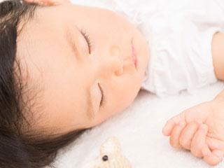 片方の耳を布団に付けて寝る赤ちゃん