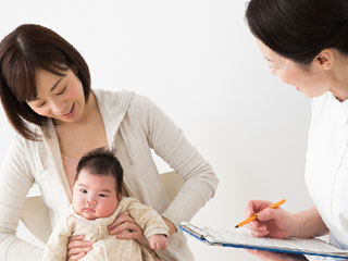 赤ちゃんを抱いた母親が看護師に質問される