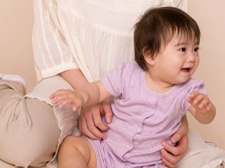 赤ちゃんを膝の間に置く母親
