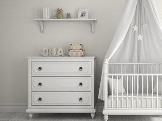 小さなタンスとベッドのある赤ちゃんの部屋