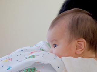 乳糖不耐症に耐え父親にしがみつく赤ちゃん