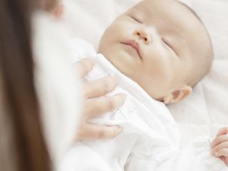ミルクが溢れて母親に拭かれる赤ちゃん
