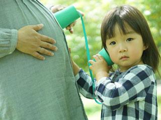 妊婦のお腹に耳を澄ます子供
