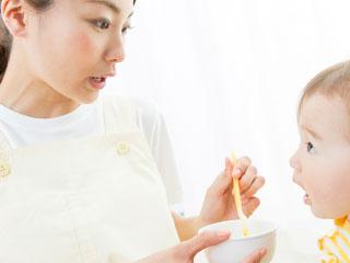 園児に離乳食を食べさせる保育士
