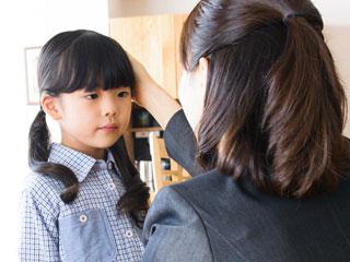 子供と話すスーツ姿の女性