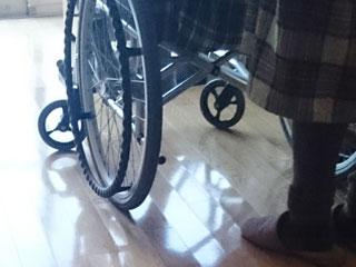 車椅子の後ろに立つ主婦