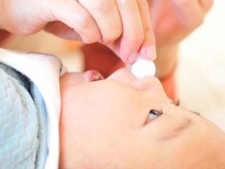 鼻水吸い取り器を鼻に当てられる赤ちゃん