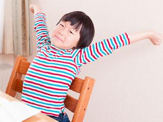 勉強机の前で背伸びする子供