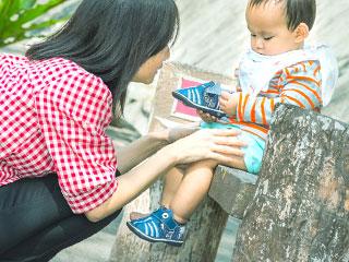 公園のベンチに赤ちゃんを座らせる母親