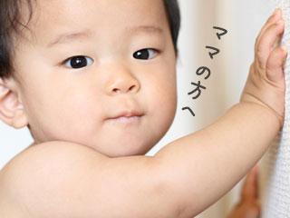 壁に寄りかかって立つ赤ちゃん