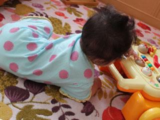 ベビーマットの上で玩具に触る赤ちゃん