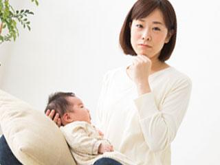 赤ちゃんを膝に載せて考える母親