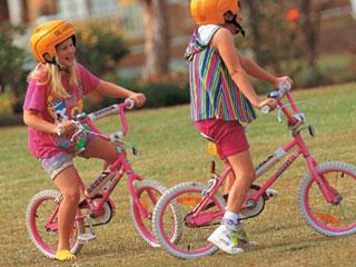 自転車にまたがって地面に足を置く子供達
