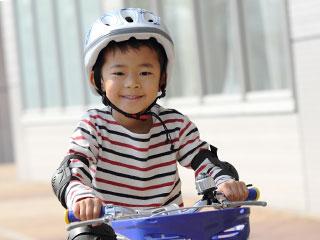 ヘルメットを被って自転車に乗る子供