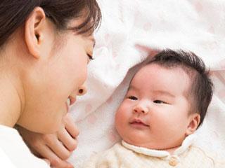 赤ちゃんと一緒に横になる母親