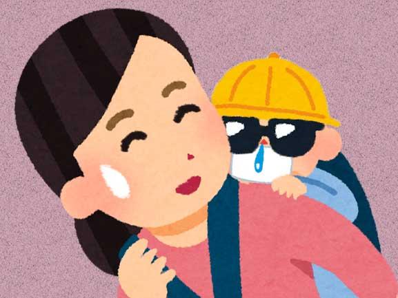 帽子とマスクとサングラスをして母親におんぶされている赤ちゃん