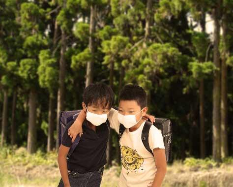 杉並木をマスクをして歩く小学生
