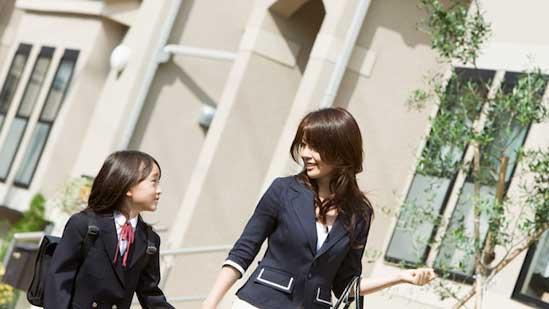 私立小学校の入学式に向かう男の子と母親