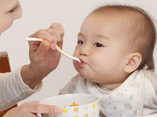 母親から離乳食を貰う赤ちゃん