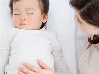 眠る赤ちゃんのお腹に手を置く母親
