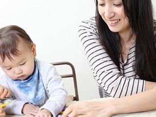 母親と一緒に玩具をいじる赤ちゃん