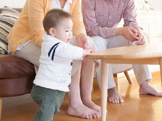 つかまり立ちをする赤ちゃんを見守る母親