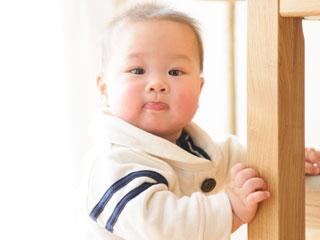 柱につかまって立つ赤ちゃん