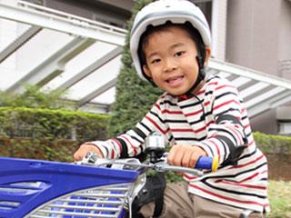 ヘルメットを被って自転車に乗る男の子